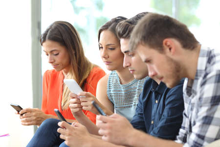 Addicted group of friends using their smart phones at the same time at home Stock Photo