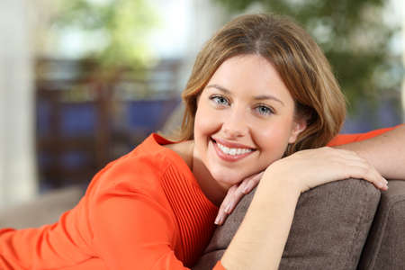 Happy woman posing sitting on a couch at home looking at camera Stock Photo