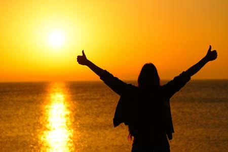 Vista posteriore ritratto di una silhouette di donna felice gesticolando pollici in su le braccia tese celebrando il successo all'alba