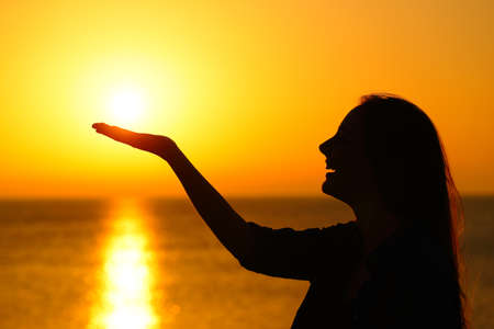 Side vire portrait of a woman silhouette holding sun at sunrise on the beach