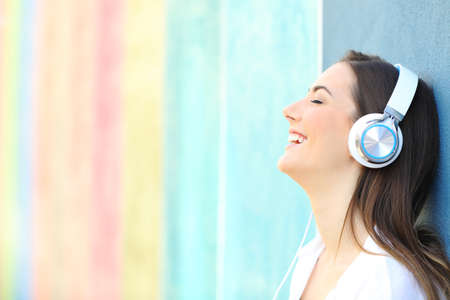 Side view portrait of a happy girl listening to music on a colorful wall Banco de Imagens