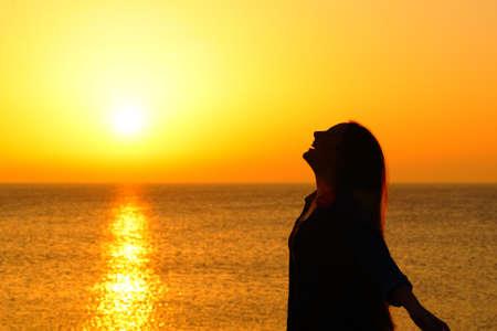 Zijaanzichtportret van een gelukkig vrouwensilhouet op het strand dat bij zonsondergang ademt