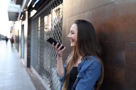 Happy girl using voice recognition on smart phone leaning on a wall in the street