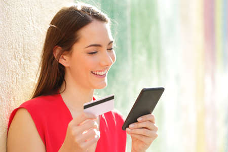 Happy woman pays online with credit card and smart phone in a colorful street Stock Photo