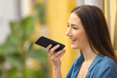 Side view portrait of a happy girl using voice recognition on smart phone in a colorful street