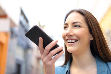 Happy girl using voice recognition app on smart phone walking in the street
