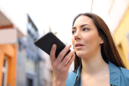 Serious girl using voice recognition app on smart phone walking in the street