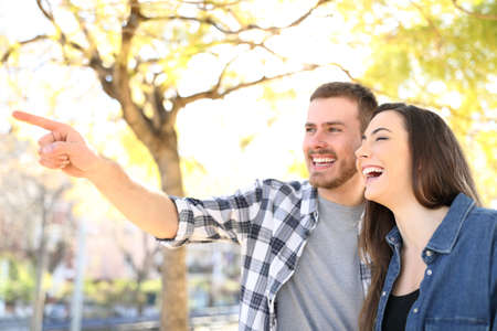 Happy couple pointing away laughing in a park with trees in the background
