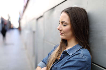 Side view portrait of a sad girl complaining alone in the street