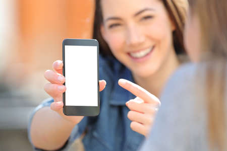 Close up of a happy woman hand showing a blank smart phone screen to a friend in the street Banque d'images - 119003836
