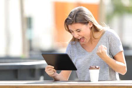 Podekscytowana dziewczyna znajdująca treści online na tablecie siedząca w parku w słoneczny dzień