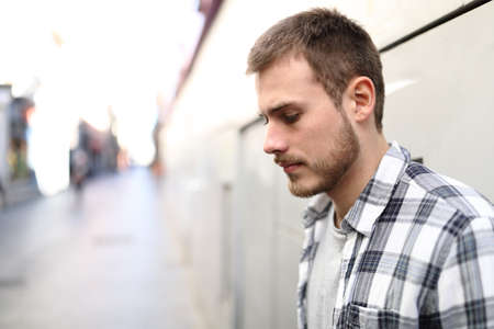 Side view portrait of a sad man complaining alone in the street