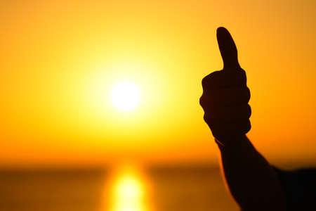 Nahaufnahme einer Frauenhandsilhouette, die bei Sonnenuntergang mit einer warmen Sonne im Hintergrund den Daumen nach oben gestikuliert