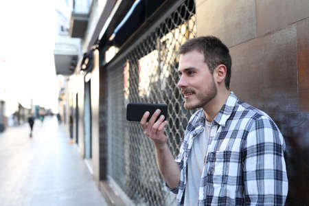 Guy using voice recognition on smart phone outside in the street of an old town