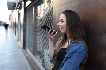 Girl using voice recognition on smart phone outside in a street of an old town