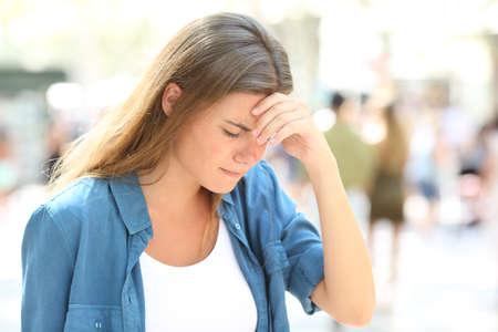 Fille douloureuse souffrant de maux de tête debout dans la rue