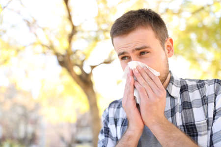 Ill or allergic man coughing in spring season in a park