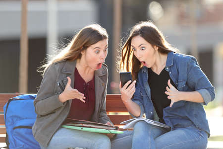 Two amazed students checking smart phone content sitting on a bench in a park