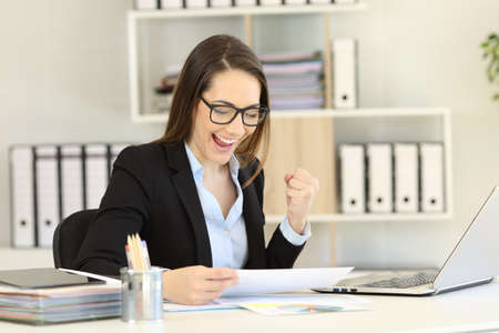 Excited businesswoman checking gorwth graph celebrating success at office