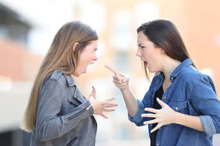 Two angry women fighting shouting each other in the middle of the street Zdjęcie Seryjne