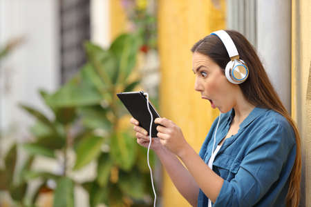 Chica sorprendida escuchando y viendo contenido en línea de tableta en la calle