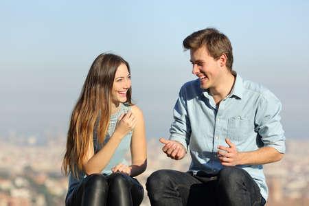 Coppia felice parlando seduto in una periferia della città una giornata di sole