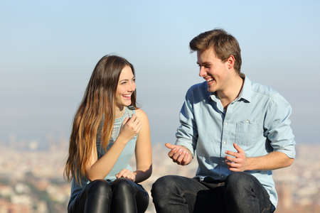 Happy couple talking sitting in a city outskirts a sunny day