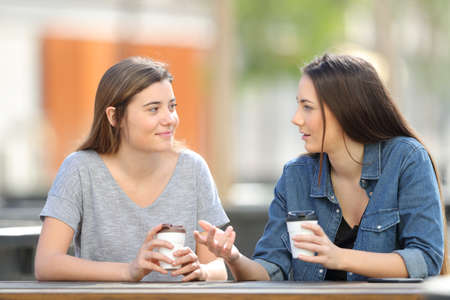 Two casual friends talking in a park drinking coffee