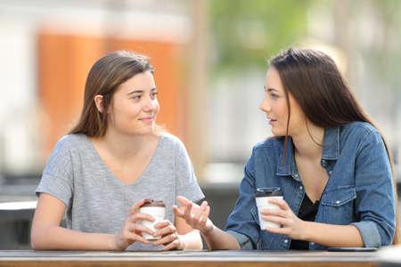 Zwei zufällige Freunde unterhalten sich in einem Park und trinken Kaffee