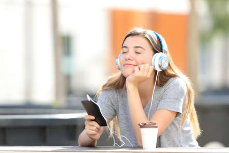 Relaxed girl listening to music from smart phone sitting alone in a park