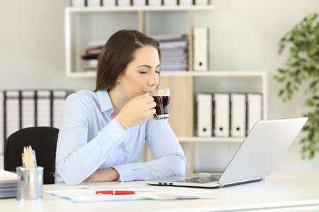 Office worker relaxing drinking coffee enjoying flavour