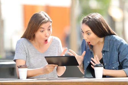 Two amazed friends watching media content in a tablet sitting in a park