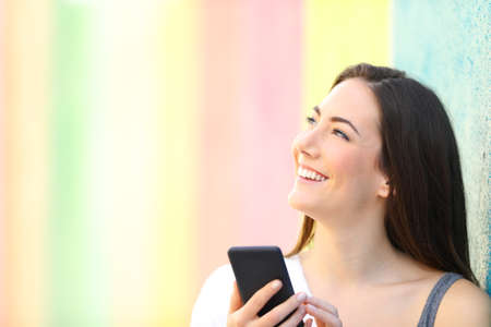 Happy girl holding smart phone thinking looking at side in a colorful street