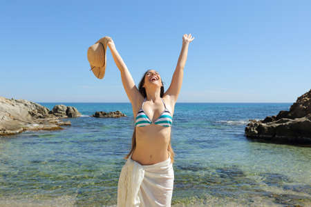 Happy tourist raising arms celebrating vacation on a beautiful beach on summer