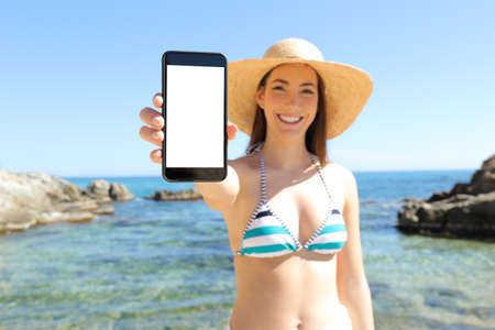Front view portrait of a happy tourist in bikini showing blank vertical smart phone screen on the beach on summer vacation