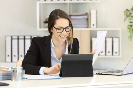 Happy office worker working comparing paper documents online on a tablet