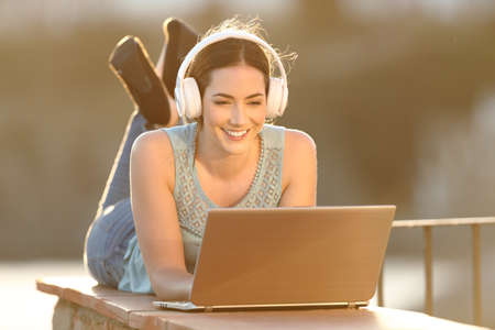 Happy woman with headphones watching media on laptop lying on a balcony wall
