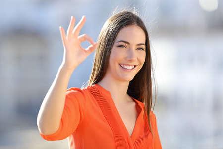 Mujer feliz en naranja gesticulando bien firmar mirando a la cámara en una ciudad en las afueras de un día soleado Foto de archivo