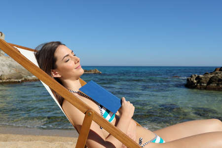 Side view portrait of a relaxed tourist sleeping sitting on a deckchair on the beach holding a book Stock Photo