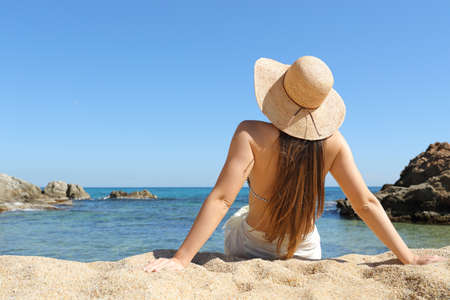 Back view portrait of a sunbather relaxing sitting on the sand of the beach on summer vacation