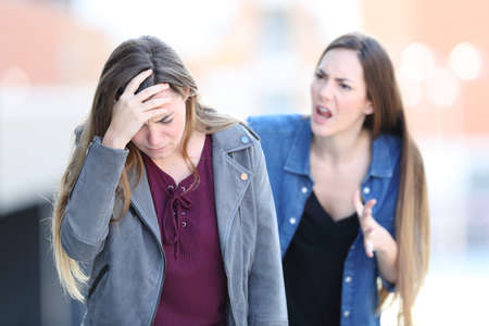 Mad girl scolding her concerned friend in the street Stock Photo