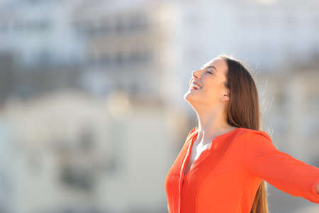 Side view portrait of a joyful woman in orange breathing deep fresh air outdoors in a town outskirts