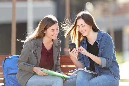 Two happy students checking smart phone content sitting on a bench in a park Stock Photo