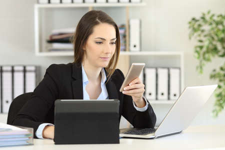 Busy businesswoman using multiple devices a phone laptop and tablet at office
