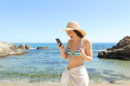 Excited tourist checking smart phone content on summer vacation on the beach