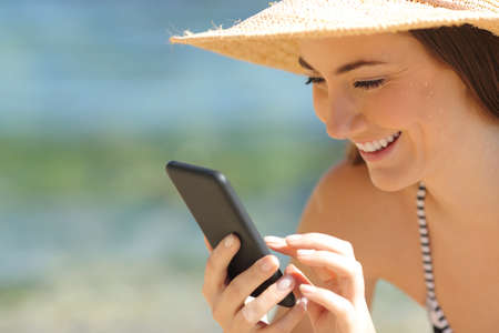 Detail of a happy tourist using smart phone on the beach on summer vacation