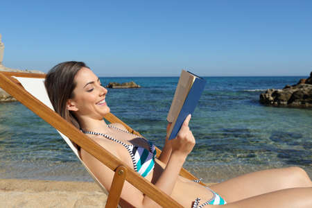 Side view portrait of a happy woman in bikini reading a paper book on the beach on summer vacation