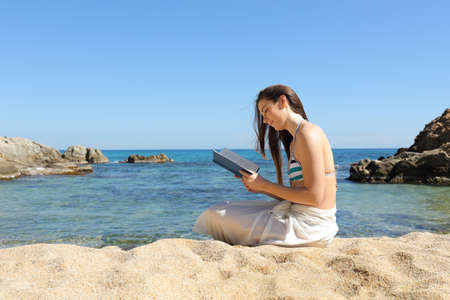 Relaxed tourist sitting on the sand of the beach reading a paper book on summer vacation