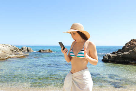 Surprised tourist checking smart phone on the beach on summer vacation Stock Photo