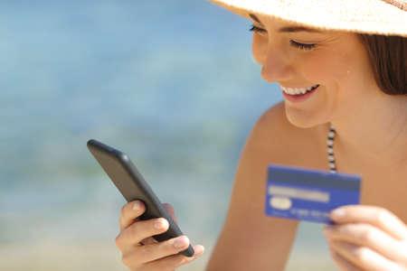 Glücklicher Tourist, der in den Sommerferien online mit Kreditkarte und Smartphone am Strand bezahlt